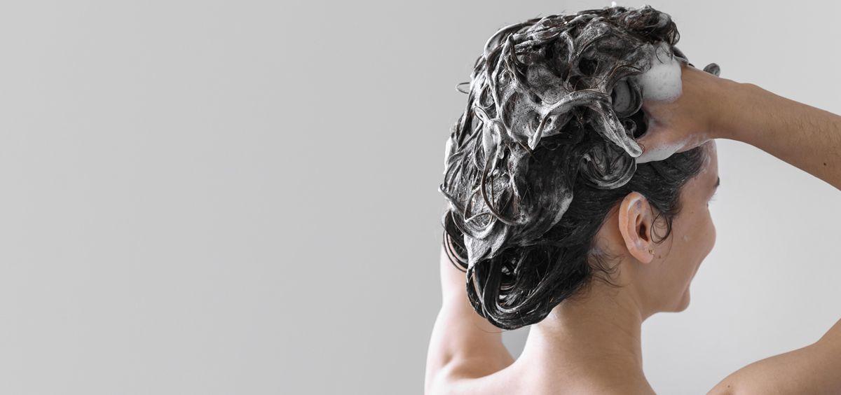 Mujer con champú en el cabello (Foto. Freepik)
