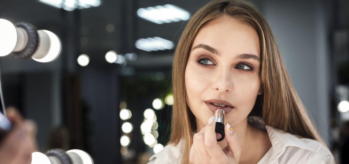 Mujer pintándose los labios (Foto. Freepik)