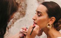 Mujer maquillando a otra (Foto. Lara Onac)