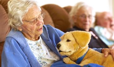 Anciana con demencia junto al perro robot (Foto: Tombot)