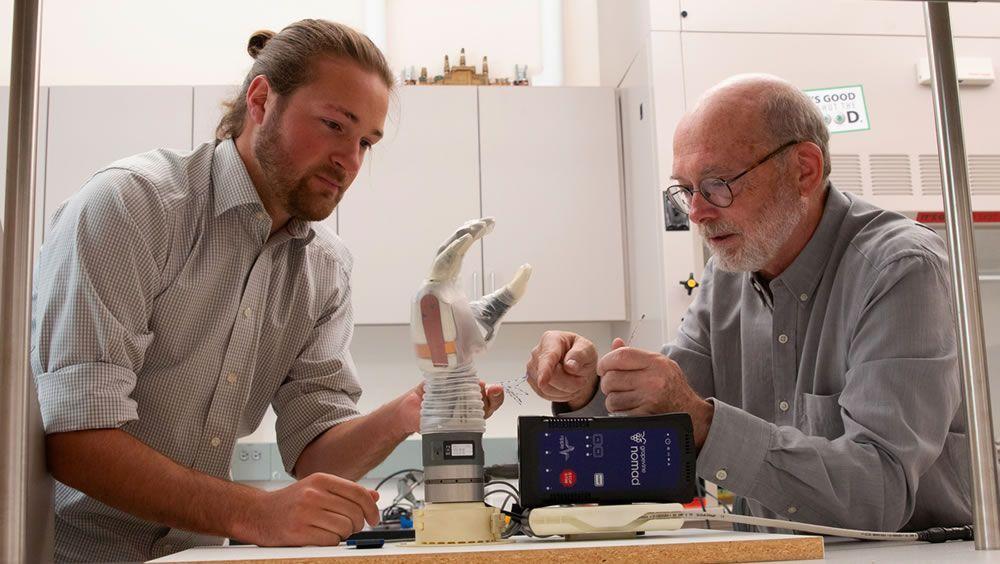 Los investigadores, junto al brazo protésico que han impulsado (Foto: Dan Hixson - Colegio de Ingeniería de la Universidad de Utah)