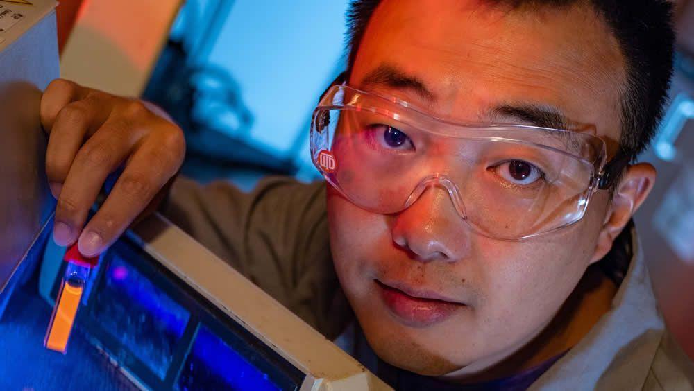 El estudiante graduado de la Universidad de Rice, Bo Jiang, muestra un vial fluorescente (Foto. Universidad de Rice)