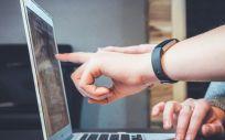 Dos personas utilizando un ordenador para consultar datos.Foto de John Schnobrich en Unsplash.
