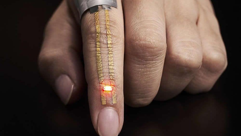 La corriente eléctrica desde una batería flexible colocada cerca del nudillo fluye a través del conductor y potencia el LED justo debajo de la uña. 2017 Someya Laboratory.