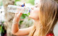 Mujer hidratándose por ola de calor (Foto. Freepik)
