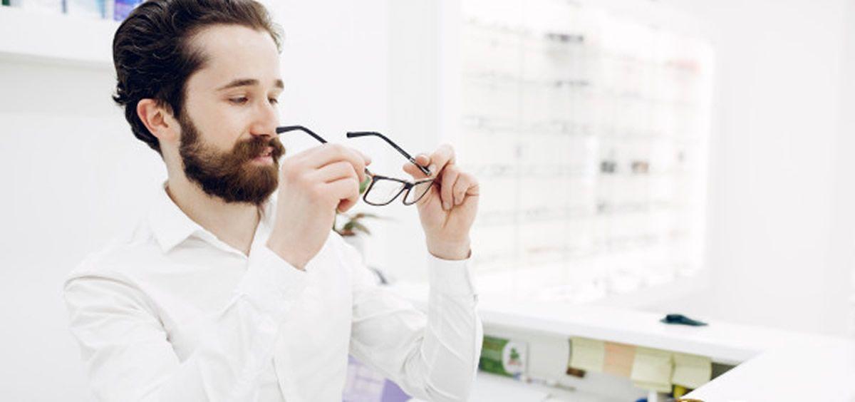 Hombre probandose gafas en una óptica (Foto. Freepik)