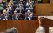 Enrique Ruiz Escudero, sentado a la izquierda en la primera fila, escucha a Isabel Díaz Ayuso (Foto: Flickr PP de Madrid)