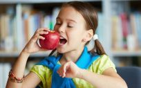 NIña comiendo manzana en la escuela (Foto. Freepik)
