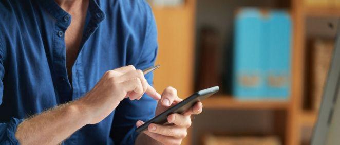 Hombre usando su teléfono móvil mientras trabaja en casa (Foto: Freepik)