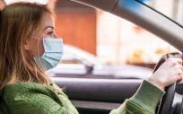 Una mujer con mascarilla conduciendo un vehículo (Foto: Freepik)