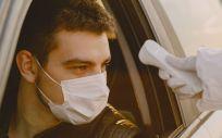 Profesional protegido toma la temperatura de una persona (Foto: Freepik)