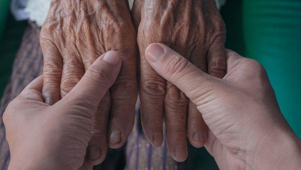 Manos de una persona mayor tomadas por otra persona joven (Foto: Freepik)