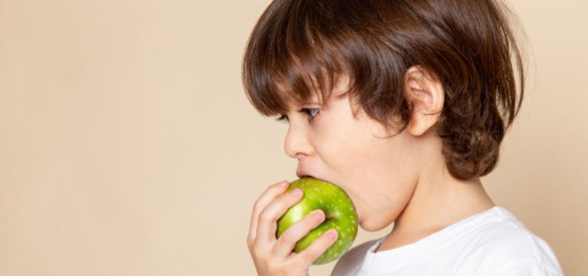 Niño comiendo fruta (Foto. Freepik)