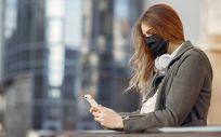 Una mujer joven con mascarilla usa su teléfono móvil (Foto: Freepik)