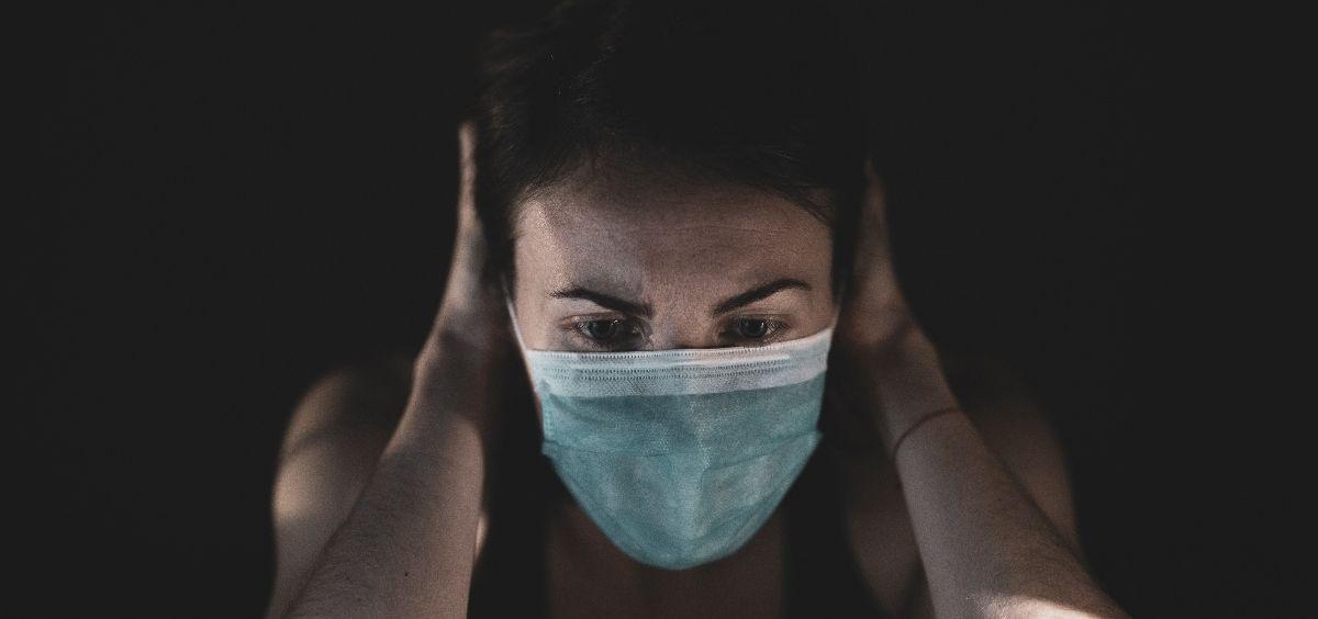 Una mujer con mascarilla estresada por la pandemia. (Foto. Unsplash)