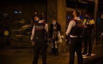 Varios Mossos d'Esquadra paran a una persona durante un control por el toque de queda impuesto a raíz de la crisis sanitaria del Covid 19 (Foto. David Zorrakino   Europa Press)