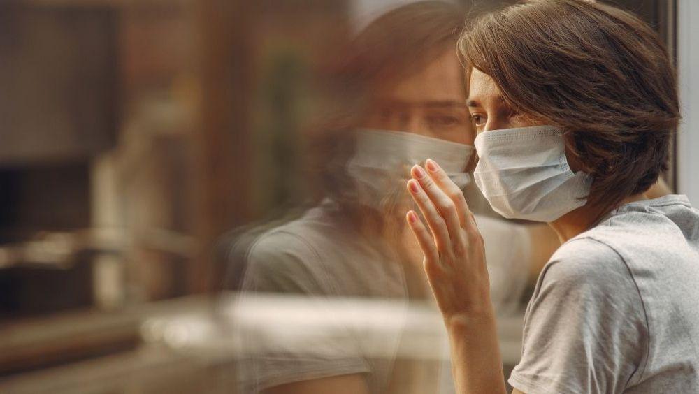 Una mujer con mascarilla se asoma a una ventana (Foto: Freepik)