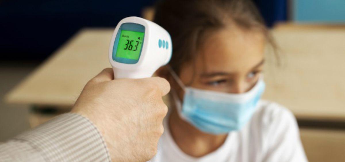 Profesora toma la temperatura a una alumna (Foto. Freepik)