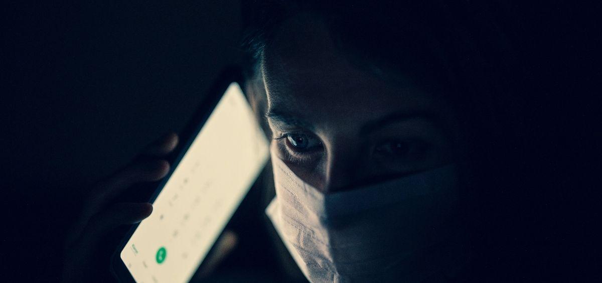 Una persona protegida con mascarilla utilizando su teléfono móvil para una emergencia. (Foto. Unsplash)