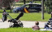 Una madre sentada en el césped junto a su hija ven pasar un coche de la Policía Nacional (Foto. Rober Solsona   Europa Press )