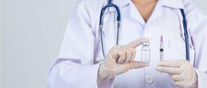 Una profesional sanitaria sostiene una jeringuilla y un vial de una vacuna (Foto: Freepik)