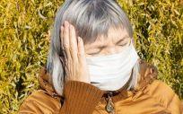 Una mujer con mascarilla sufre dolor de cabeza (Foto. freepik)