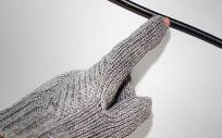 La yema del dedo de un guante de detección de voltaje inalámbrico se ilumina cuando la mano del usuario se acerca a un cable activo. (Foto. Universidad de Purdue)