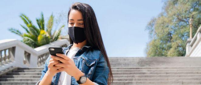 Una chica joven con mascarilla mirando su teléfono móvil (Foto: Freepik)
