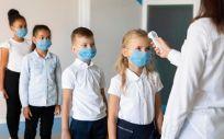 Profesora tomando la temperatura a los alumnos antes de acceder al aula (Foto. Freepik)