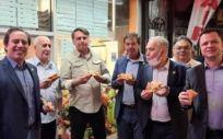 Jair Bolsonaro comiendo pizza con el presidente del Banco Federal de Caixa Económica, Pedro Guimaraes, y varios ministros en Nueva York (Foto. @GILSONMACHADONETO / Reuters)