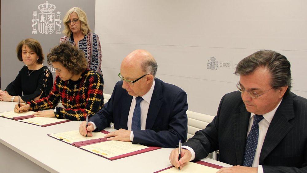 Dolors Montserrat, ministra de Sanidad, Cristóbal Montoro, de Hacienda, y Jesús Acebillo, presidente de Farmaindustria, firmando el acuerdo.