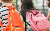 Escolares con mochilas, camino de clase